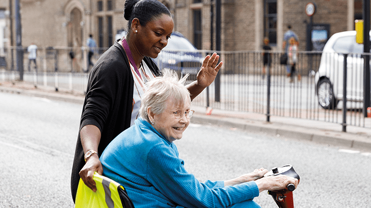 Care worker supports elderly woman crossing the road